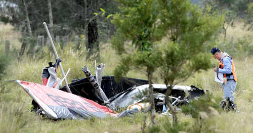 Crash probed: An investigator from the Recreational Aviation Association inspects the wreckage of the ultralight at the crash site near Tatham on Saturday.