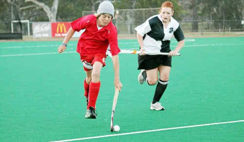 Under 15s AJ Duncan and Harlequins Melanie Eyears battle it out in ladies hockey on Saturday.