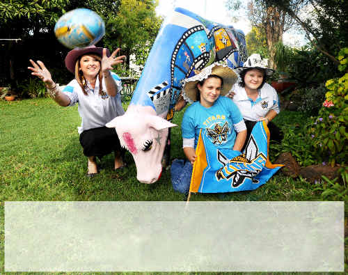 Beef Week Queen entrants (from left) Kasey-Lee Flack, Claire Carey and Melissa Gray help to promote Beef Week using Titans merchandise and the colourful Beef Week Picasso cow.