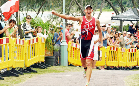 Bryce McMaster shows his jubilation after winning the elite men's division of the Byron Bay Triathlon on Saturday.