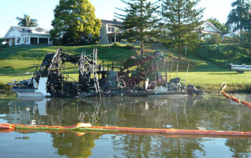 DESTROYED AND DAMAGED: The remains of Des Clarke's houseboat, above left, and Ron Skinner's damaged cruiser, above, after a fire took hold of the vessels on the Clarence River early Saturday.