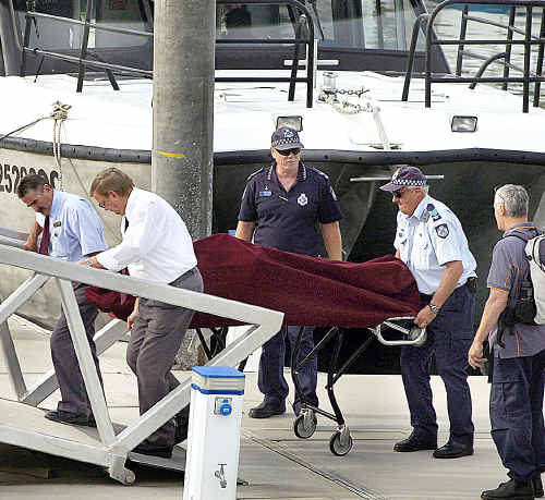 The body of a Korean tourist who died in Fraser Island's Lake Wabby (below) is brought back to the mainland at Hervey Bay marina on Saturday.