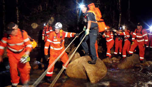 Finch Hatton-based Queensland Ambulance Service advanced care paramedic Doug Buchannan, centre on rock, and Mirani SES vertical rescue operator Mike Sarich help volunteers cross a creek at Finch Hatton Gorge.