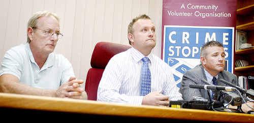 Vicki Hunter's husband Ian (left) and son Jason (centre) with Acting Detective Inspector Steve Riznyk.