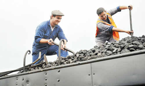 Fireman Luke Bowen and his assistant Craig Stevens shovelling coal for steam locomotive 3237 while it takes on passengers at Coffs Harbour yesterday.