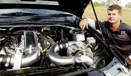 Car buff Shane Baker, of Casino, shows off the highly-modified V8 engine of his SS Commodore 355 at the Summerland Drag Races in Casino yesterday.