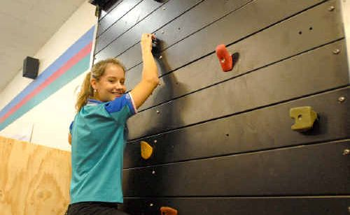 Sam Nutt, a trainer at City Fitness Health Club, climbs the new Sky Wall.