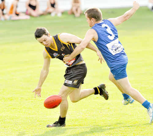 Sean Duroux of the Grafton Tigers taps the ball on despite the attention of the North Coffs defender, in a game earlier this season.