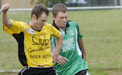 Goonellabah's Dave Annetts (left) works hard to keep possession from a Maclean opponent in their Solo Cup knockout match at Weston Park, Goonellabah, on Saturday.