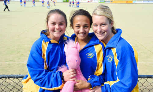 South Coast visitors Kalindi Commerford, Kizziah Plumb and Kate McKinley huddle up with their team mascot yesterday.