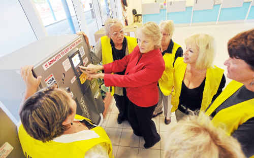 Airport carpark ambassadors are briefed on the new equipment by Therese Murray-Prior.