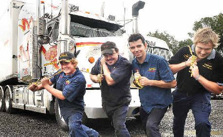 Heave-ho: Showing off their strongman skills in preparation for Saturday's Australia's Strongest Man are Hernes Freight Service employees (from left) Trent Schaefer, Jamie Lavis, Simon Balzer and Josh Herne, trying to budge a 25-tonne semi-trailer.