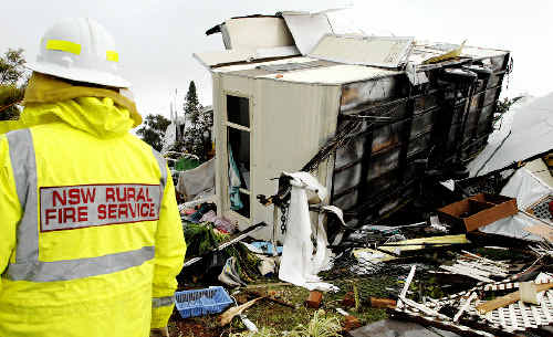 WRECKED: A NSW Rural Fire Service firefighter inspects a wreckedcaravan at the Lake Ainsworth Caravan Park after yesterday's tornado.