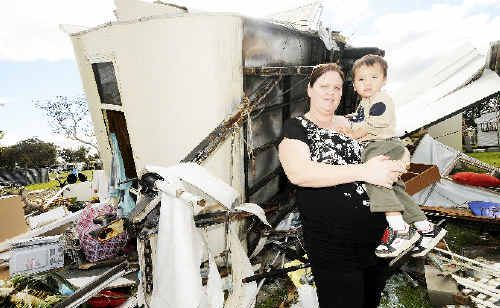Alison Kaihau, of Kyogle, and her 22-month-old son, Tane, with the destroyed caravan that belonged to her parents. Alison is grateful her family was not in Lennox on Thursday.