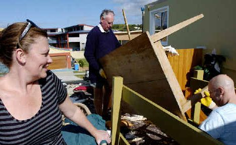 Lennox rebounds: Dodie Bischoff watches as her husband Tony (right) and long-time Lennox Head resident and neighbour John Stewart collect debris from their tornado-ravaged home in Pacific Parade on Saturday.