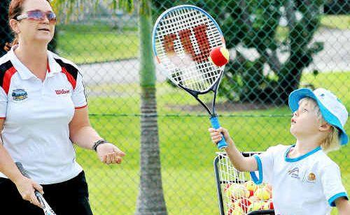 Coach Alison Scott shows Owen Stone a few pointers at Westside Tennis Club.