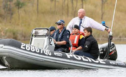 Police escort a man around Wivenhoe Dam to re-trace the movements of the canoe that capsized on Monday.