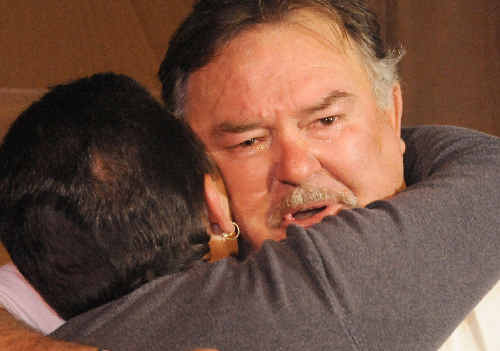 A teary Geoffrey Smith hugs a fellow patient after hearing Jayant Patel's guilty verdict.
