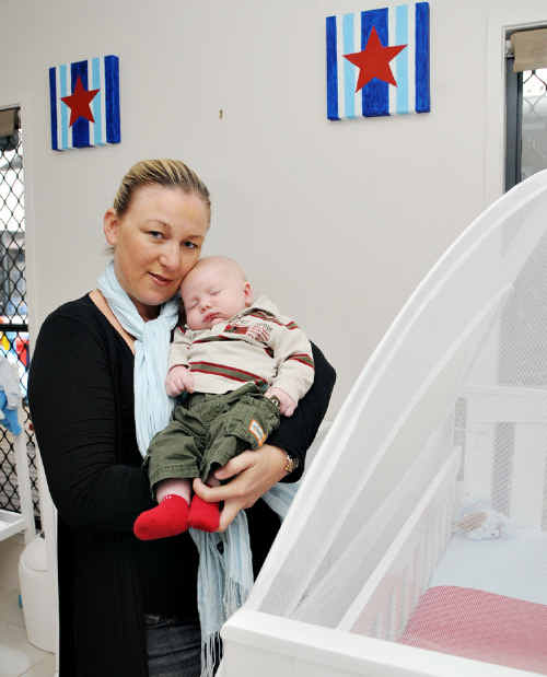 Cherie Studt-Hancock with son Cruz in front of the bare nursery wall.