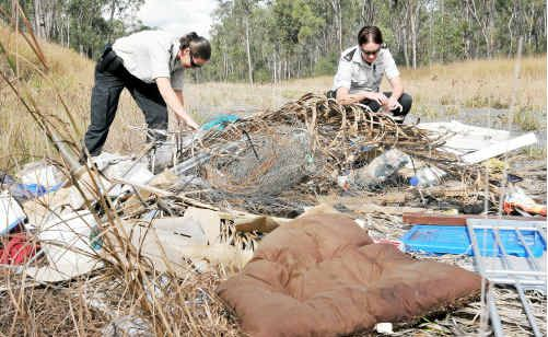 Inspecting an illegal rubbish dump on Mylrea Road, near Yarwun, are officers Sarah Kummerow (left) and Tamara Brumby.