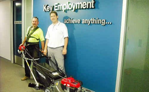 Steven Thomas with his new mower and brush cutter, presented to him by Key Employment consultant Steve Keenes.