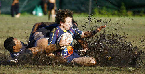 Evans Heads' Aaron Sells (right) takes an early bath in the slosh during the Bombers' NRRRL match against Lower Clarence at Evans Head on Saturday.