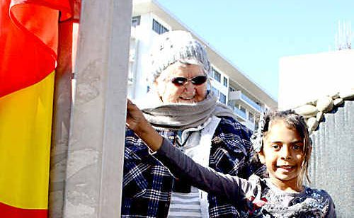 """Elder """"Aunty"""" Fay with Cidnee Young of Toowoomba raising the Aboriginal flag to launch NAIDOC Week celebrations."""