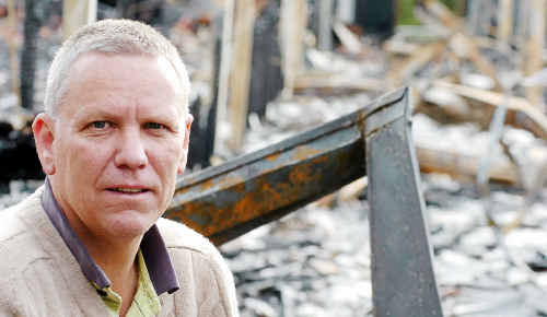 Scots PGC College principal Michael Harding in front of the charred remains of the former junior boys' dormitory last year, tenders to rebuild were opened yesterday.
