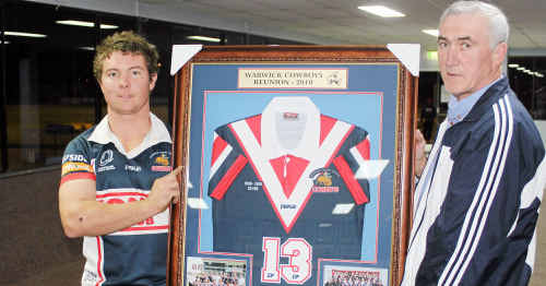 Warwick Cowboys 2010 club captain Ryan McIvor and inaugural 1986 A-grade captain Brian Dunne with one of 17 framed jerseys to be auctioned at 25th anniversary celebrations.