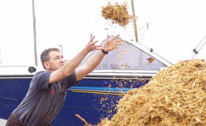 Wet start: Disco Marine owner Jason Disson, from Grafton, was kept busy yesterday spreading woodchips over the soggy ground on his site at the Yellow Pages 4WD Caravan Camping & Marine Show at the Lismore Showground.