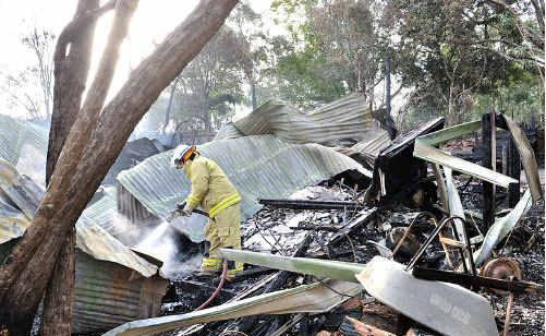 A fire fighter douses the smouldering remains of a house destroyed by fire at Montville.
