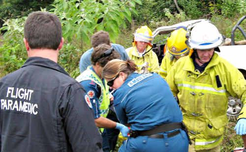 Rescue services personnel respond to a single vehicle rollover near Maleny.