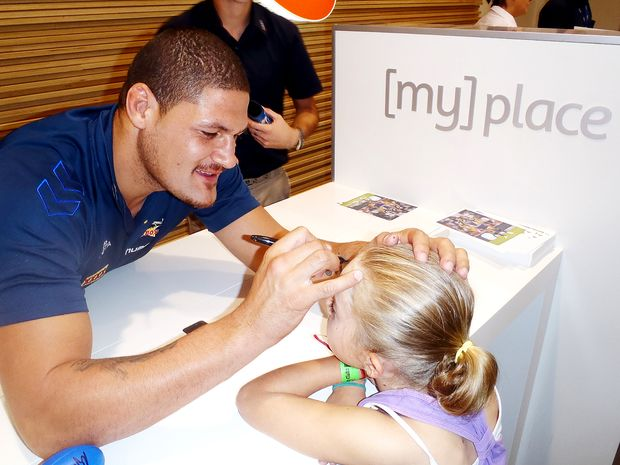 Willie Mason signing Kayla Stridiron's forehead at Telstra Store Whitsundays on Saturday. That night she put sticky tape on her forehead when she had a shower, so it wouldn't wash off.