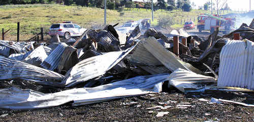 Police forensics and fire crews investigate the cause of a Witta house blaze.