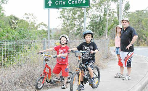 Infrastructure Services spokesman Cr Matt Burnett with children Mitchell, Josh and Jessi at the corner of Dixon Drive and Glenlyon Road, Telina.