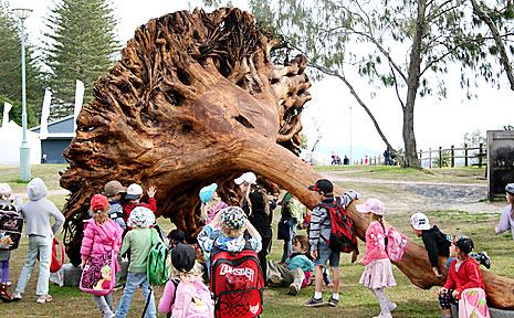 Children get a close look at John Dahlsen's camphor stump sculpture on the Byron Bay beachfront.
