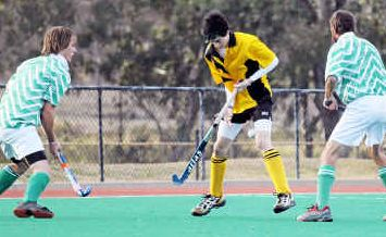 Jesse Ollerton (centre), of Corinthians, goes on the attack against Wyverns in men's hockey.