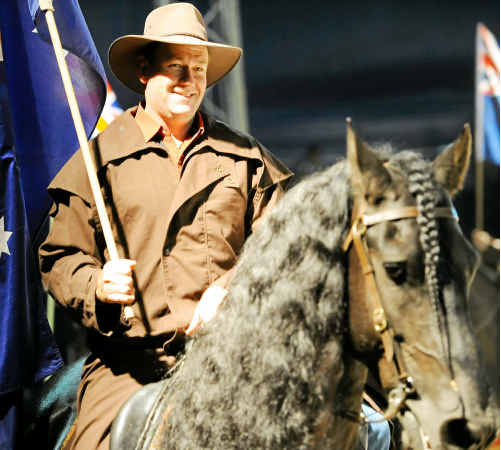 Performers at The Horseman from Snowy River proudly carry the Australian flag around the ring.