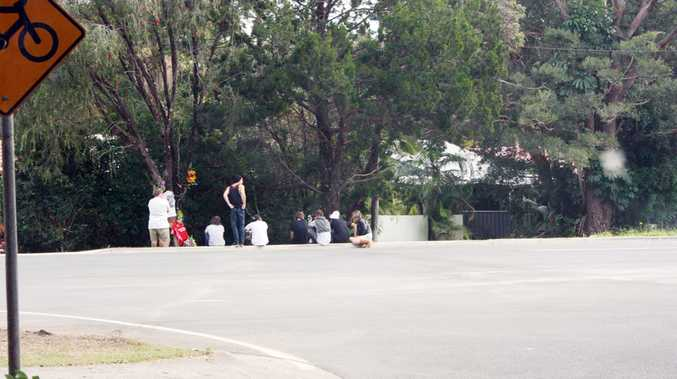 Grieving friends gather at the accident site in Bangalow Road on Monday.