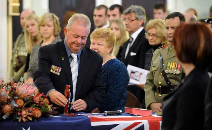 The father of Pte Nathan Bewes, Gary, places a cross on his coffin during today's service.