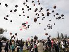 The congregation releases brown balloons, the same colour as the Justine Jones' hair, to honour her memory.