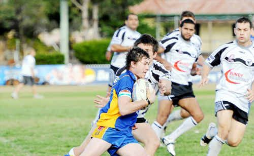Mark Annetts of Across The Waves gets tackled by Reece Maughan of Easts.