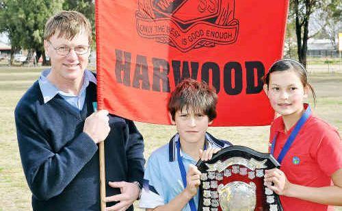Alan Olsen presents the Olsen Shield to Harwood House captains Sean Austin-Walsh and Aimee Van Der Hulst.