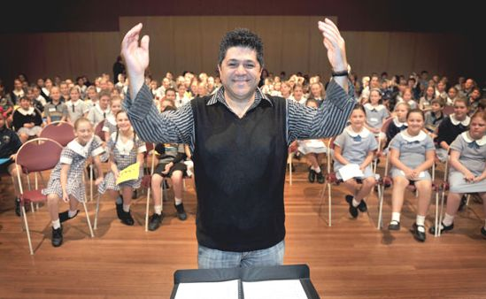 Famous New South Wales conductor George Torbay puts a host of young Coast singers through their paces at the Lake Kawana Community Centre.