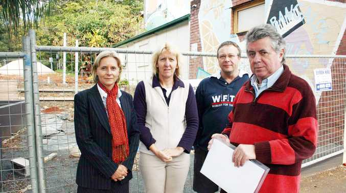 Michael Malloy (right) with Nicole Swain from the Bangalow Post Office and Carolyn Adams and Richard Rombouts from the Bangalow Newsagency, both businesses adjoining the 'half-finished pile of rubble'.
