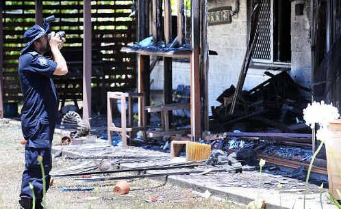 Police investigate the site of the fire and alleged attack.