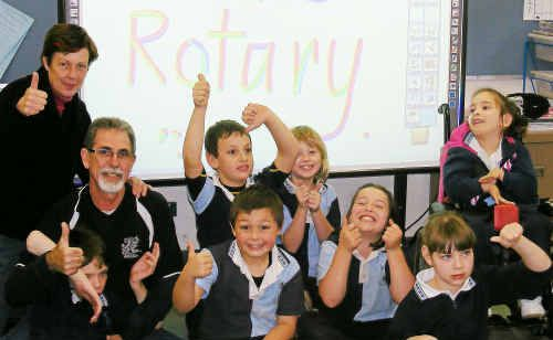 Warwick East special education unit representative Jill Cumming, with Rotarian Larry James and pupils in front of the smartboard.