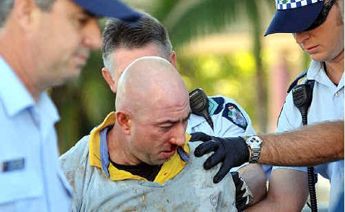 Police take a man into custody after a fight in Mooloolaba yesterday morning. The man had one of his fingers almost bitten off.