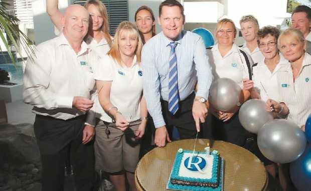 CELEBRATIONS: Rumba general manager Bill Darby, centre, takes time off with his staff to reflect on a year in business and to enjoy a piece of cake.