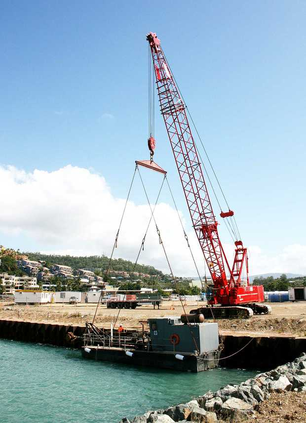 A crane lifting the dredge boat into the Port of Airlie last Friday, to remove any excess mud that has settled in the port.